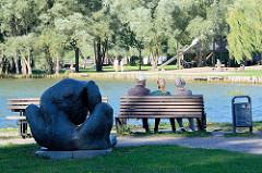 Ruhebank mit ParkbesucherInnen im Kulturpark Neubrandenburg - Skulptur am Seeufer.