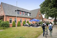 Altes Schulgebäude an der Schulstraße in Maschen; jetzt Nutzung als Restaurant mit Außengastronomie.
