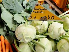 Auf dem Wilhelmsburger Wochenmarkt wird Gemüse aus Moorwerder angeboten; frischer Moorwerder Kohlrabi liegt in der Kiste, daneben frische Möhren.