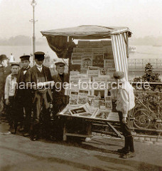 Zeitungsstand mit Zeitungsjungen am Hamburger Jungfernstieg, im Hintergrund die Binnenalster.