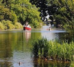 Der Ernst-August-Kanal ist ein interessantes Freizeitrevier in Hamburg Wilhelmsburg. Ein Motorboot fährt den Kanal Richtung Ernst-August-Schleuse, Kanuten paddeln.