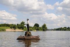 """Auf der Süderelbe bei Hamburg Stillhorn schwimmt eine der vier Holzskulpturen die zu dem Gesamtkunstwerk """"Vier Männer auf Bojen"""" gehören."""