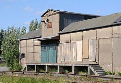 Ein stillgelegtes Lagergebäude einer Hamburger Spedition mit Gleisanschluss - die Gleise sind mit Wildkraut überwuchert.