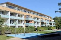 Kleiner Kinderspielplatz mit Schaukel und Karussell an der Balkon-Front / Sonnenseite eines Neubaus in Hamburg Bramfeld.