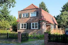 Backsteinarchitektur der 1930er Jahre - Stadtvilla mit Blendgiebel und Krüppelwalmdach, Holzläden an den Fenstern.  Architekturfotos aus Hamburg Fuhlsbüttel.