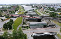 Im Vordergrund hinter der Wilhelmsburger Brücke das Müggenburger Sperrwerk und die S-Bahnstation Veddel - ein roter S-Bahnzug steht an der Haltestelle.