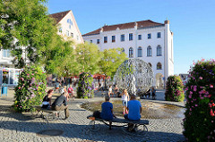 Neuer Markt von Waren - Trinkbrunnen, Bildhauer Walther Preik. Ruhebänke mit BesucherInnen in der Sonne - im Hintergrund das neue Rathaus.