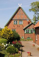 Bauernhaus mit Fachwerkgiebel in Hamburg Stillhorn; im Vorgarten blühen Pfingstrosen, die Fensterrahmen sind in regionaltypischem Grün gestrichen.