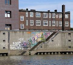 Im Billehafen führt eine Treppe hinunter zum Wasser des Hafenbeckens - die Wand ist mit buntem Graffiti bedeckt. Hinter der Kaimauer die dunkelroten Klinker eines der historische Gebäude am Billehafen.
