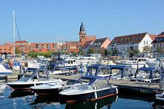 Sportboothafen / Marina in Waren an der Müritz; Sportboote mit Bimini, Sonnensegel / Bimini am Steg - im Hintergrund die St. Marienkirche.