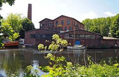 Blick über den Veringkanal zum Industriegebäude mit hohem Schornstein, das 1906 errichtet wurde.