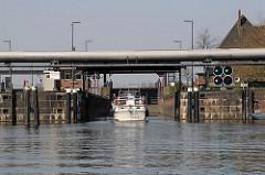 Das Schleusentor ist geöffnet, das grüne Signallicht an der Tideschleuse gewährt die Einfahrt für das Sportboot, das aus dem Tiefstackkanal kommt.