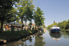 Biergarten am Ufer des Ernst-August-Kanals; Sonnenschirme und Tische stehem auf der Wiese am Wasser.