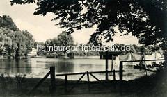 Historische Ansicht vom Mühlenteich in Hamburg Fuhlsbüttel; Stacheldrahtzaun und Holzgatter, Wäsche ist zum Trocknen aufgehängt. Im Hintergrund  die Brücke Ratsmühlendamm.