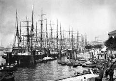 Historische Aufnahme vom Hamburger Niederhafen; Ruderboote liegen am Ponton - Segelschiffe an den Dalben.
