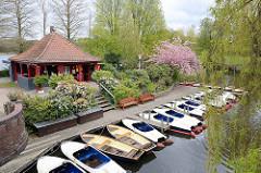 Frühling in Hamburg - Blick auf die Liebesinsel  im Stadtparksee;Tretboote am Steg, roter Pavillon und rosa blühende Zierkirsche.