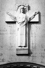 Segnende Jesusfigur am Kreuz über dem Eingang der katholischen Herz-Jesu-Kirche in Stettin.