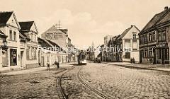 Historische Ansicht von der Hauptstraße in Roßlau; Werbung für Drogen, Farben, Wein, Zigarren an einer Hausfassade, eine Straßenbahn steht an einer Haltestelle.