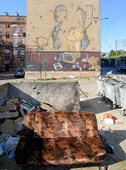 Blick über eine Müllkippe mit Sofa zu einer Wandmalerei an einem Wohnhaus im Hafenbezirk von Stettin.