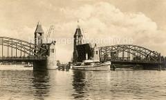 Altes Foto von der Hansabrücke über die Oder in Stettin; die Klappbrücke ist hochgefahren, eine Barkasse fährt durch die Öffnung - auf der Brücke stehen die wartenden Menschen dicht gedrängt.