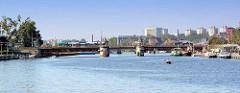 Blick über die Oder zur Autobrücke in Stettin; Fahrgastschiffe und Sportboote liegen an der Promenade - im Hintergrund Hochhäuser.