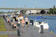SpaziergängerInnen und Sportboote an der Stettiner Uferpromenade der Oder - Autobrücke über den Fluss.