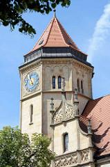 Uhrenturm mit blauem Ziffernblatt und goldenem Zeiger und Sonne / Akanthus - Fassadenschmuck, Seepferd.