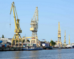 Kaianlage an der West-Oder in Stettin; Gewerbearchitektur und Hafenkräne - Schiffe liegen an der Kaimauer.