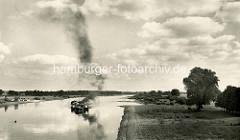 Alte Fotografie von der Elbe  bei Roßlau; ein Schiffsverband fährt flussabwärts, dicker Qualm steigt aus dem Schornstein des Schleppers.