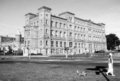 Historische Backsteinarchitektur in Stettin - Spaziergängerin mit Hund am Straßenrand.