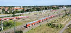 Bahngleise mit fahrenden roten Zügen in der Nähe des Hauptbahnhofsvon Dessau; Blick vom alten Räucherturm.