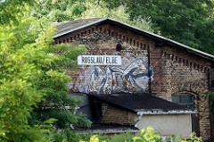 Alter Ziegelschuppen mit Graffiti am Bahnhof / Schild Roßlau Elbe.