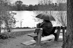Hamburger Frühling im Regen - ein Parkbesucher sitzt mit Regenschirm auf einer Bank am See im Stadtpark.