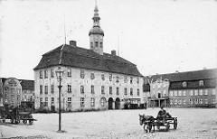 Historische Ansicht vom Barock-Rathaus in Neubrandenburg - Pferdefuhrwerke auf dem Marktplatz.