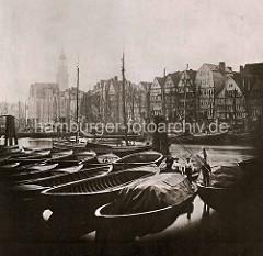 Historische Fotografie vom Hamburger Binnenhafen; Ewerführer stehen auf ihren Booten; im Hintergrund die Masten der Segelschiffe.