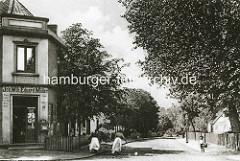 Historische Fotografie  vom alten Hamburger Stadtteil Winterhude; Blick in die Ohlsdorfstraße, zwei Frauen schieben einen Karren - ein Junge mit Strohhut und Korb steht am Straßenrand; links die Einmündung der Himmelstraße