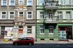 Alt + neu, Wohnhaus mit vernageltem  Balkon, daneben ein renoviertes Pendant mit schmiedeeisernen Balkongitter und farblich abgesetzter grüner Fassade.