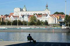Ein Angler sitzt am Ufer der Oder - am Ufer liegt ein Binnenschiff,  dahinter eine Häuserzeile mit Hotel und das Stettiner Schloss mit den grünen Turmhelmen.