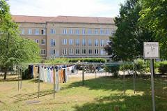 Innenhof eines Wohnblocks an der Friedrichstraße in Dessau; Wäsche hängt zum Trocknen beim Kinderspielplatz auf der Wiese.