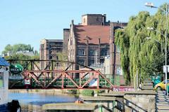 Historische Industriearchitektur / Ziegelgebäude im Hafen von Stettin; eine Eisenbrücke führt über den Hafenkanal der West-Oder