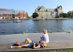 Entspannung an der Uferpromenade der Oder in Stettin; Holzbänke am Flussufer Laden in der Sonne zum Verweilen ein; man kann den Bootsverkehr auf dem Fluss beobachten.