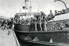Ein dicht besetztes Motorboot legt am Steg im Hamburger Hafen  am Baumwall an; Hafenarbeiter kommen von der Schicht .