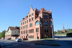 Verwaltungsgebäude mit Blendgiebel im Stettiner Bezirk Pomorzany -  im Hafenbezirk von Stettin im Hintergrund die Kirche des hl. Joseph; neogotische Kirche.