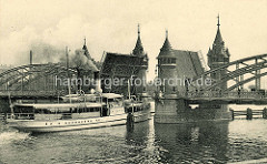 Historische Fotografie von der Bahnhofsbrücke über die Oder in Stettin, die Klappbrücke ist aufgeklappt - ein Fahrgastschiff fährt unter Dampf hindurch.