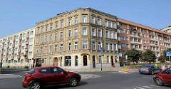 Historisches Eckgebäude mit klassizistischer Fassadengestaltung, links und rechts anschließende Neubauten mit Balkons.