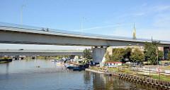 Moderne Autobrücke über einen Hafenkanal Stettiner Hafengebiet; Sportboote liegen unter der Brücke am Steg.