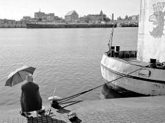 Ein Angler mit Sonnenschirm sitzt an der West-Oder im Hafengebiet von Stettin am Kai; am gegenüberliegenden Flussufer ein Binnenschiff und Hafenanlagen.