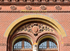 Ziegelfassade mit Bauschmuck - Reliefwappen mit Blattwerk;