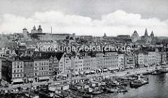 Alte Fotografie von der Uferpromenade an der Oder in Stettin. Arbeitsboote und  Barkassen liegen am Kai, die Schaufenster der Geschäfte sind vor der Sonne mit Markisen geschützt - im Hintergrund das Stettiner Schloss.