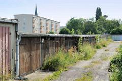 Alte Garagen mit Holztoren, die Zugänge sind mit Wildkraut zugewuchert; im Hintergrund Wohnhäuser in Dessau-Roßlau.